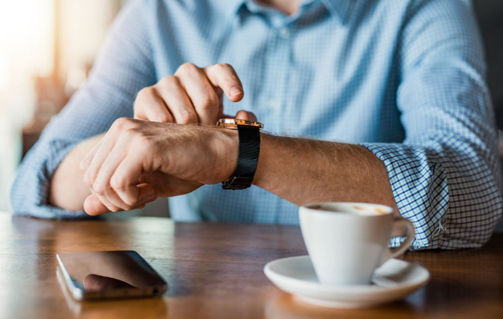 man drinking coffee checking watch