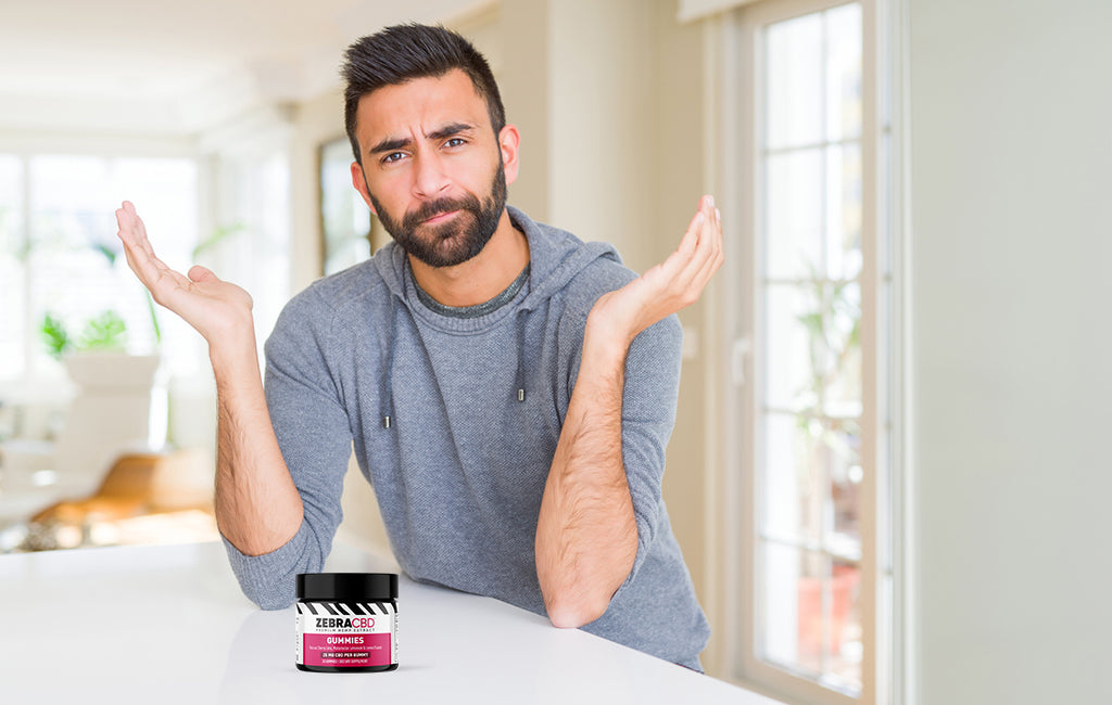 man gesturing in wonder and jar of cbd gummies