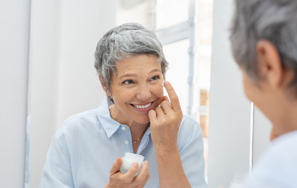 older woman putting on skin cream at mirror