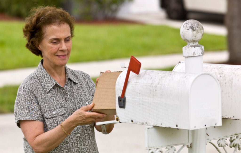 woman retrieving package from mailbox