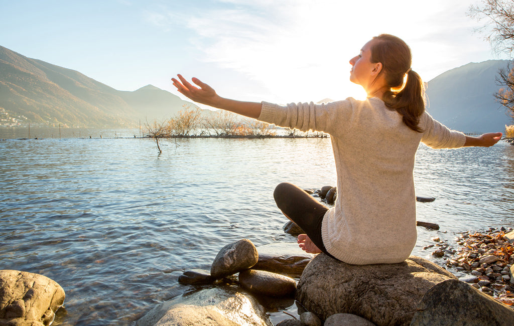 woman meditating by lake