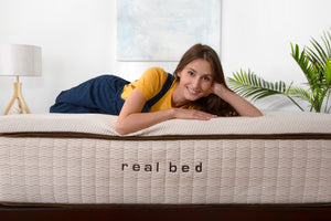 Woman Laying on a Real Bed Mattress looking at you
