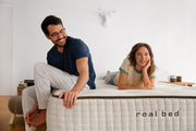 Man sitting and woman laying on a Real Bed natural mattress. Image.