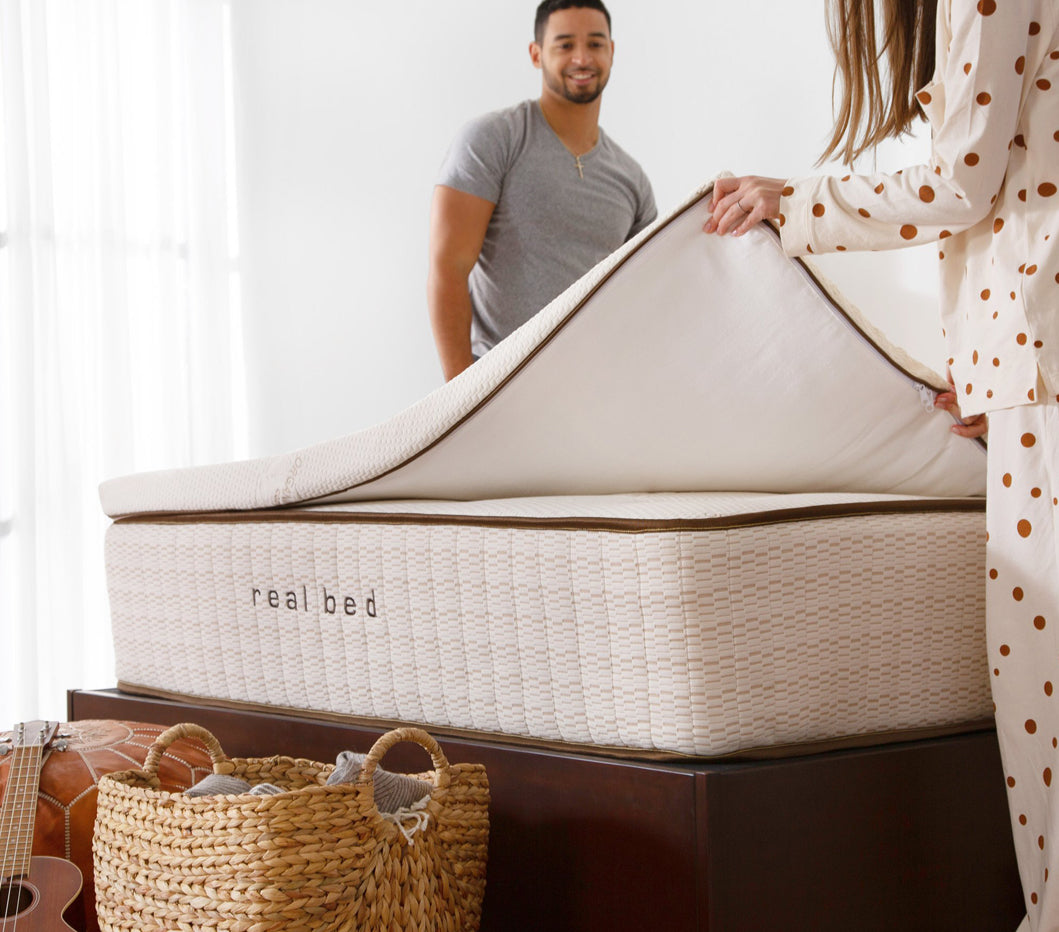 Man and woman putting on a Real Bed Topper. Image.