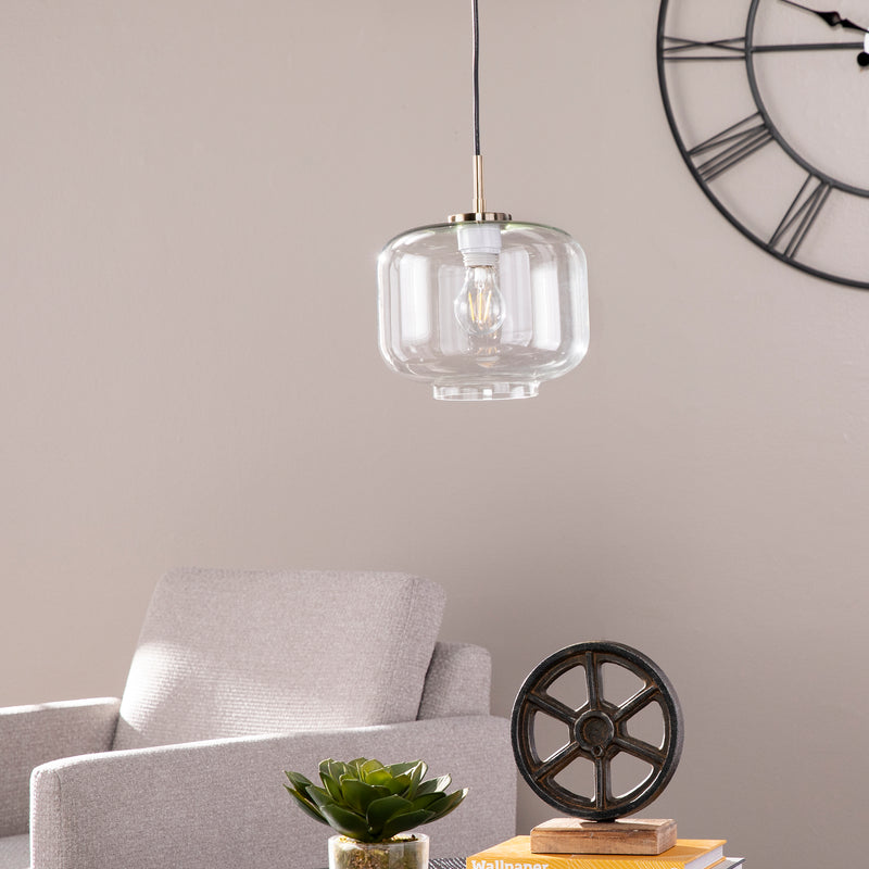 Glass pendant hanging over a table living room ceiling. Roman numeral clock in the background with upholstered accent chair.