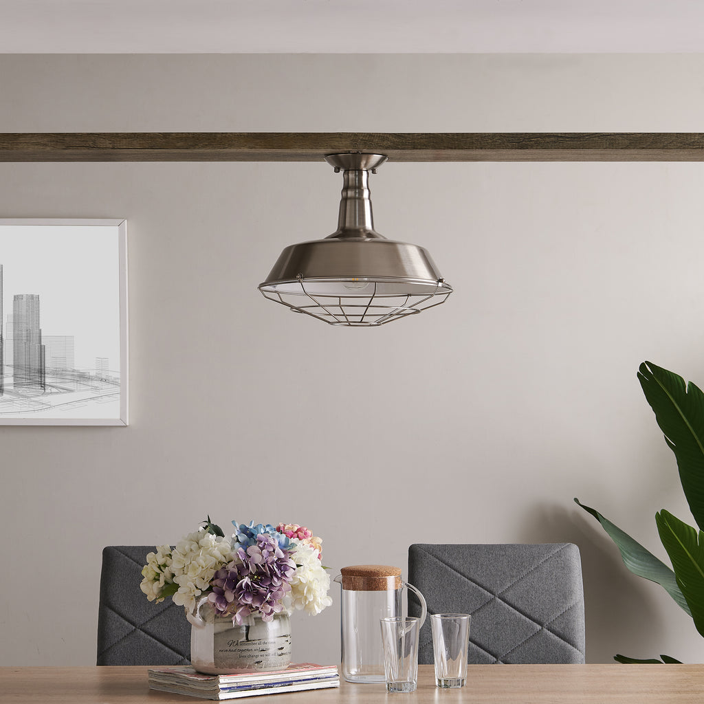 Brushed silver, flush mount pendant light shown over a kitchen table. Kitchen table has a coffee pot, with open magazines, a plant, and candle.
