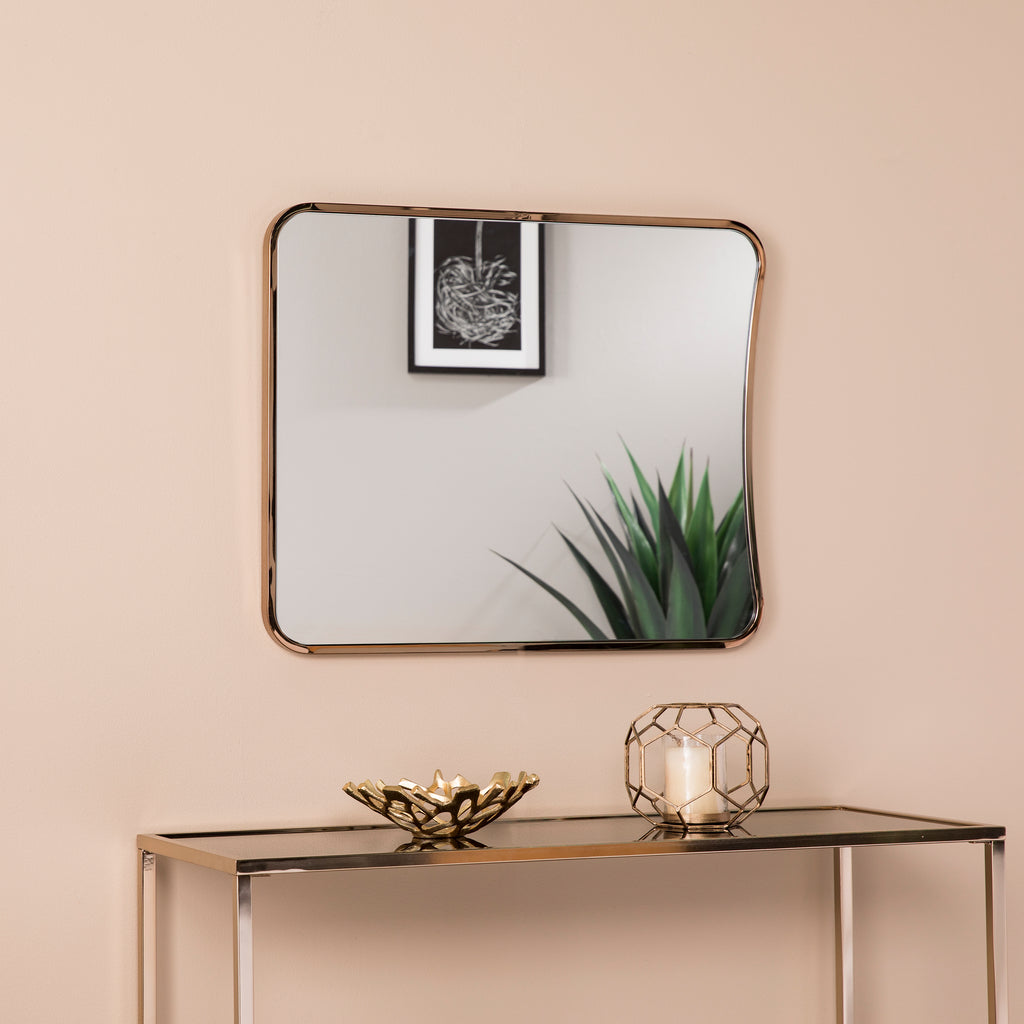 Rectangular mirror with champagne gold frame is hung above a champagne gold metal console table with decor on top.