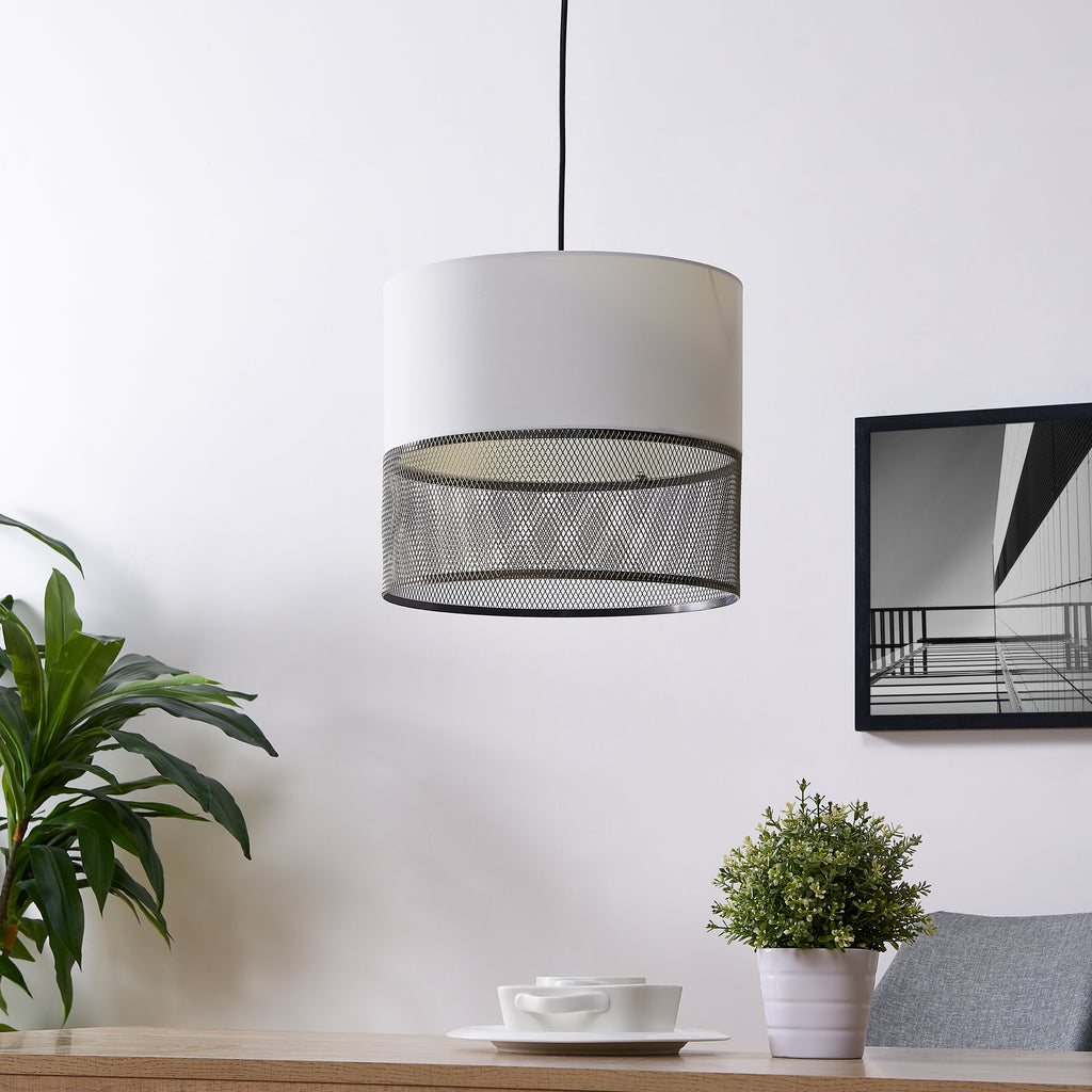 Photo of Abana pendant lamp hanging over a table. The pendant light is a fabric and mesh metal pendant light