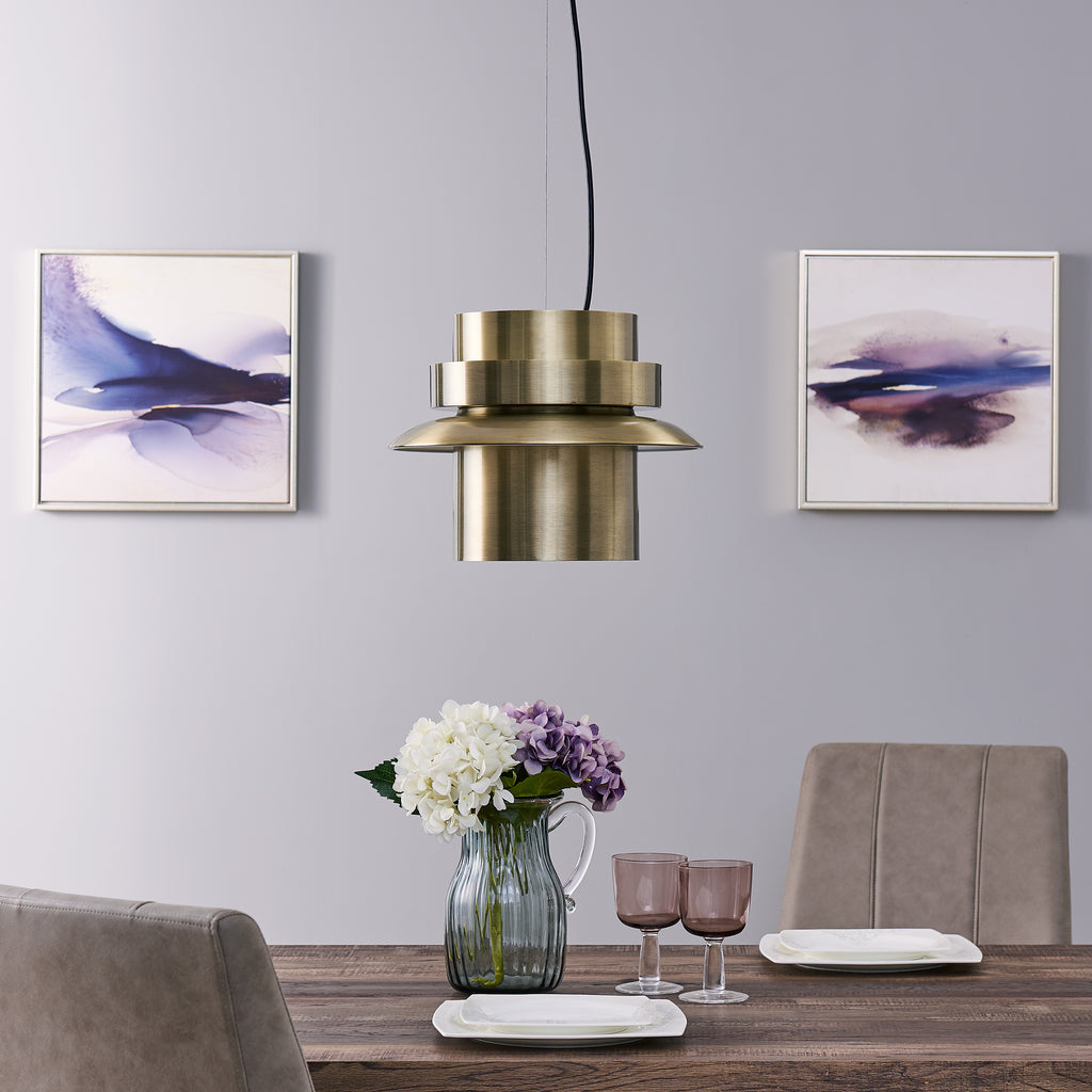 Brass pendant light hanging over a dining table with flowers and place settings for two.