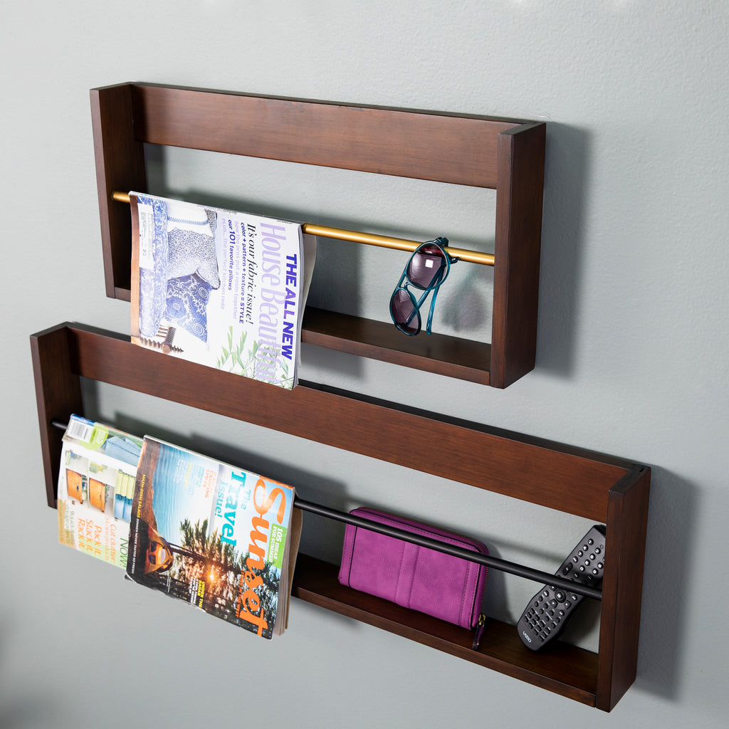 Close up angled view of the magazine set. Small shelf has one magazine and sunglasses over the bar. The large shelf shows two magazines, a wallet, and remote.