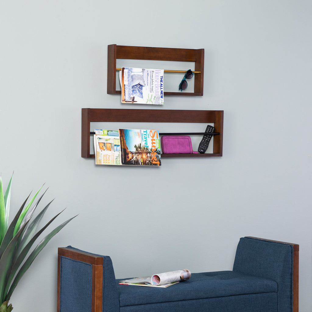 Achaz Wall Shelves are wall-mounted storage shelf set. Photo of the magazine racks mounted on the wall -the small over the large. Both mounted over a blue bench with large plant on the left side.