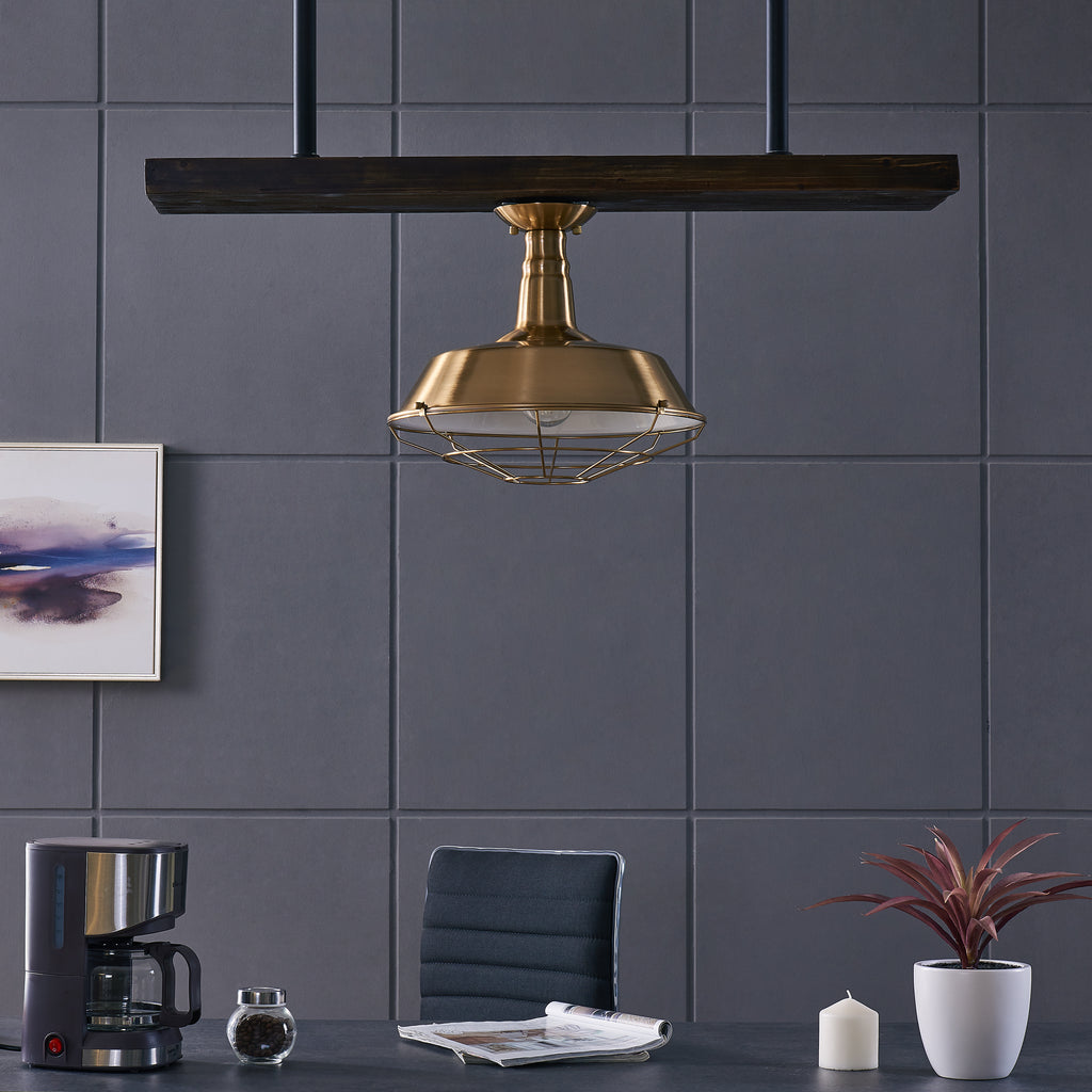 Antique brass, flush mount pendant light shown over a kitchen table. Kitchen table has a coffee pot, with open magazines, a plant, and candle.