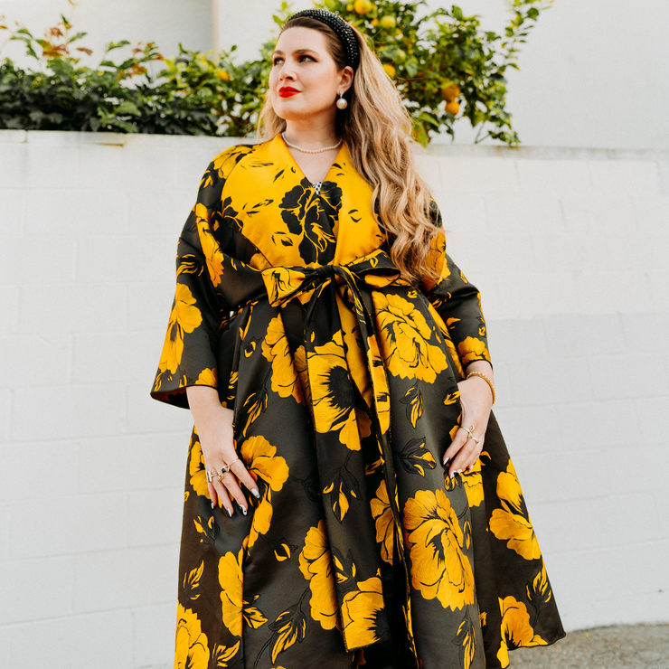 Designer Suzanne Vinnik wearing yellow jacquard floral print opera coat belted  in front of white wall with a lemon tree behind.