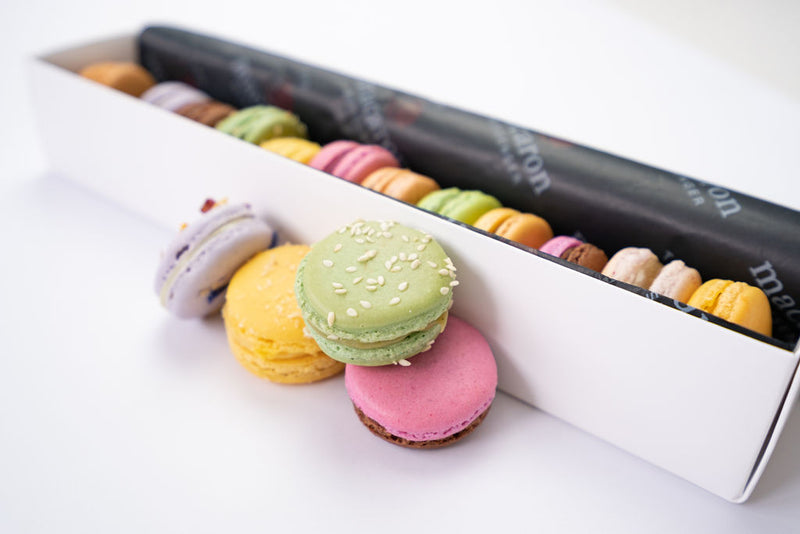 12 assorted macaron flavours in long gift box with colourful macarons