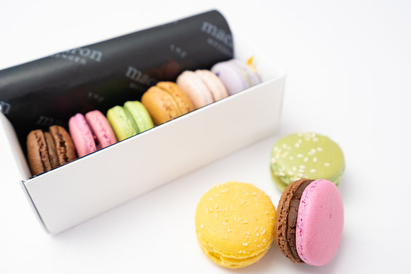 6 macaron flavours in packaging with colourful macarons arranged