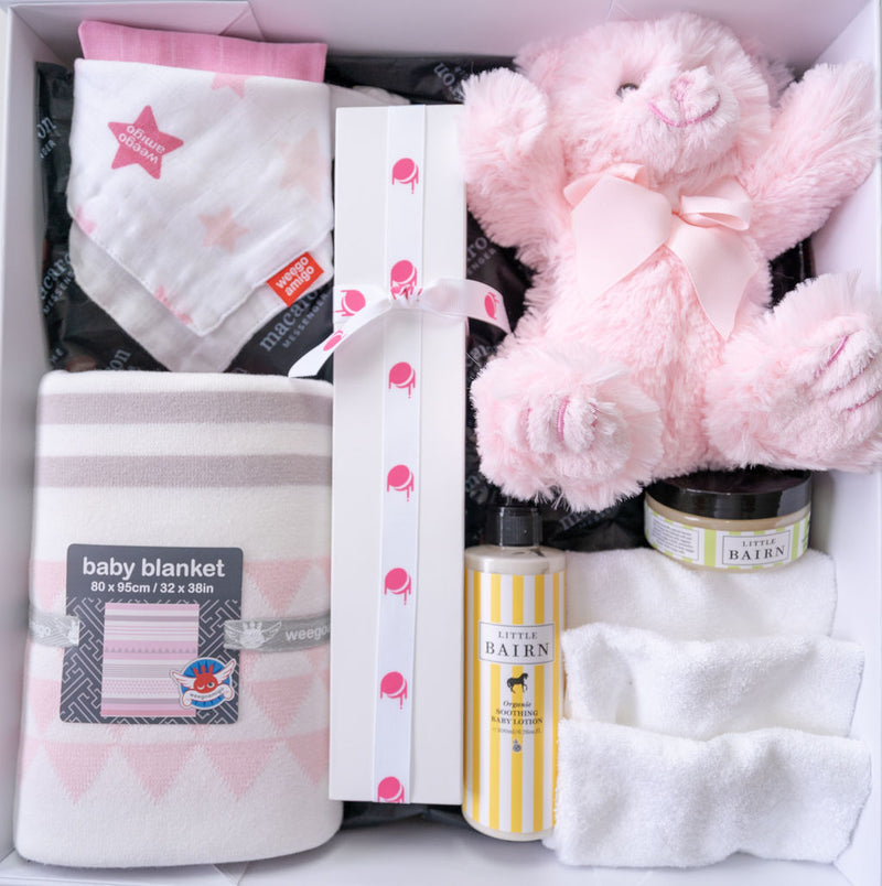 gift hamper for a baby girl with macarons and weegoamigo baby products top view