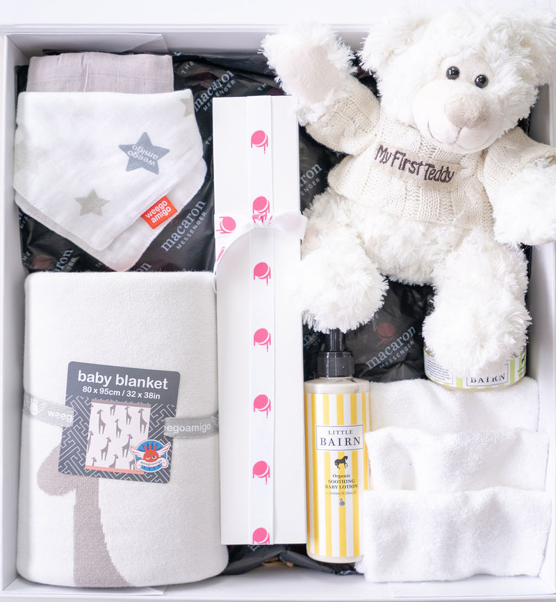 white baby gift hamper with teddy, blankets and baby products top view