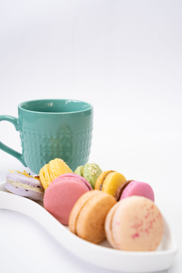 Macarons in a serving dish with a coffee cup