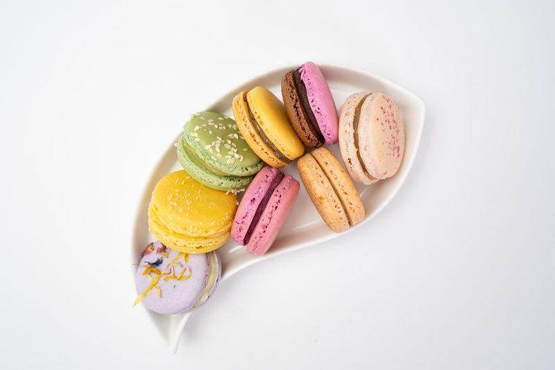 Serving dish full of mixed macaron flavours
