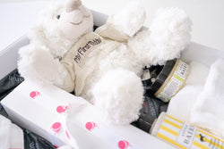 closeup of baby shower gift hamper with macarons and teddy bear