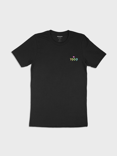 "black t-shirt with a left breast area patch-print design featuring the text ""1969"" in rainbow colors with a heart symbol above the center of the text."