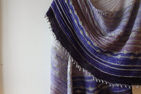 a crescent shaped shawl is pinned on a white wall. the shawl is 6 shades of purple, starting at a super pale lilac and ending in a deep violet. there is a stripe of grey between each colourchage.