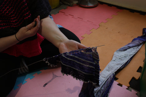 i am sat just in frame on the floor wearing black leggings. my hand stretched out to the camera holding onto part of the purple shawl that has a blocking wire starting to be woven through the top edge. you can see the blocking mats on the floor they are red, orange and pink