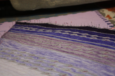 the purple shawl is pinned onto the pink mat. you can only see a small section but you can see all the colours of purple that it transitions through