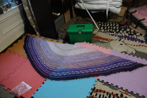 this is a photo of the purple shawl laying on the floor all pinned out. the straight edge is at the top of the photo. you can see the mats that it is on which are orange, red. blue, pink and purple. you can also see parks of my ikea rug under that, grey splodges. orange stripes, lots of cream. there is also a green plastic lidded box at the top of the shawl and the end of a black tv cabinet to the side of that.