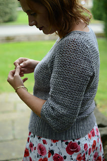 a women with  white skirt with red roses on it is looking to the left playing with her hands, wearing a beautiful light grey cardigan that has a really textured stitch pattern