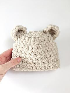 a really light cream baby hat with two tiny bear ears being held up against a white wall