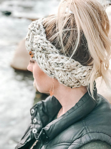 side on view of a women with light blonde hair up in a high pony tail wearing an almost braided headband crocheted in very light cream yarn. she is wearing a black leather jacket
