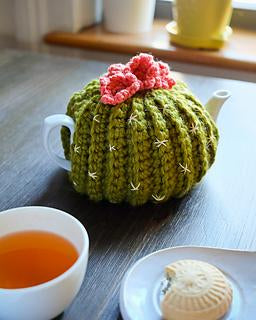 a green tea cosy in the shape of a little round cactus with little pink flowers on the top. being modelled by a white teapot with a cup of tea and a biscuit in the bottom of the image