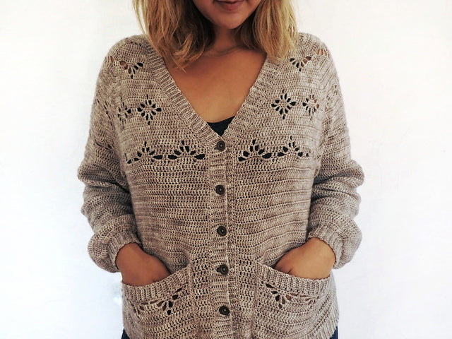women stood against a white background with hands in her cardigan pockets.  the cardigan is a grampa shape with some lace details. and it is a realy light brown