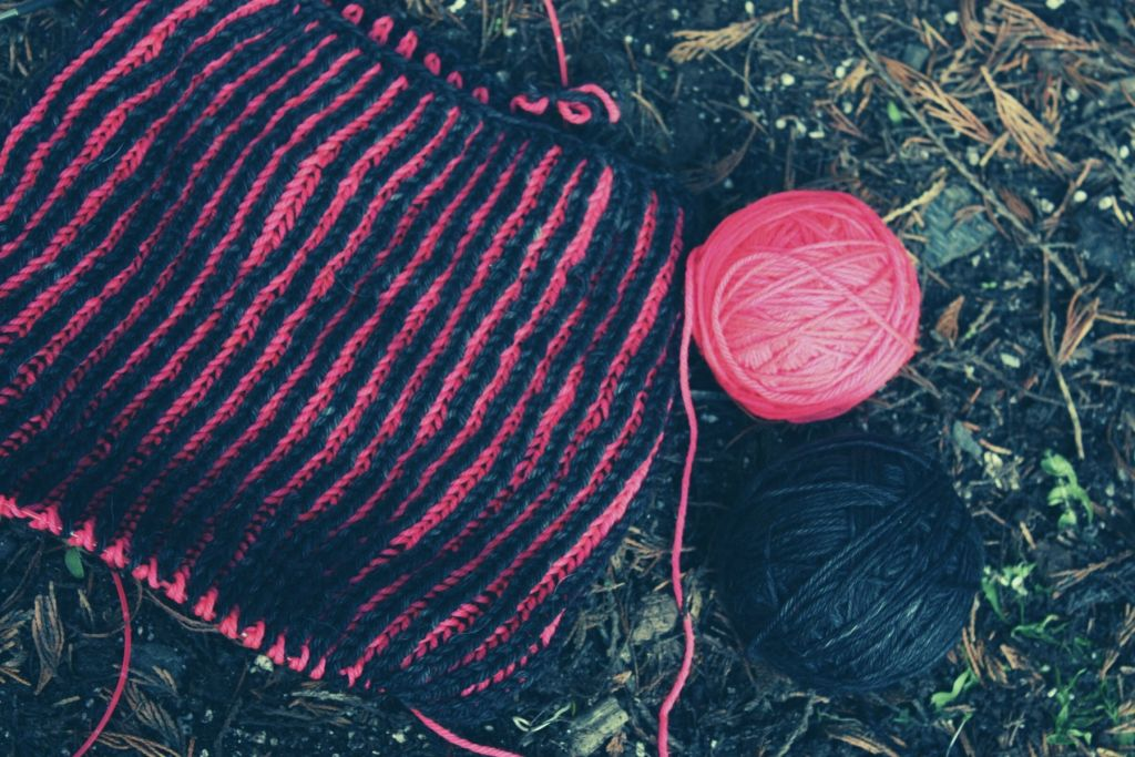 half knit brioche cowl sat on the floor with a ball of neon pink and black on the right hand side. there is some tree debris on the floor
