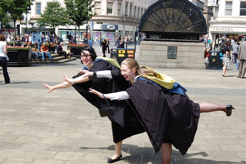 two women in the middle of the frame, flying like superman. the one in the back is me, and the one in the front is morag. we are in the city square in dundee on graduation day. both wearing our robes that are black with a blue and yellow hood