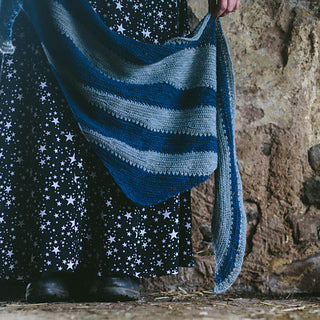 a womens legs wearing a black skirt covered in stars against a stone wall background. holding a triangle shawl that has wedges of light blue and wedges of denim blue