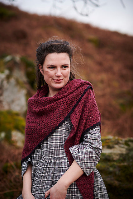 a women with a cheeky smille, standing in the middle of some moorlands wearing a grey and white checked dress. she is wearing a deep red shawl
