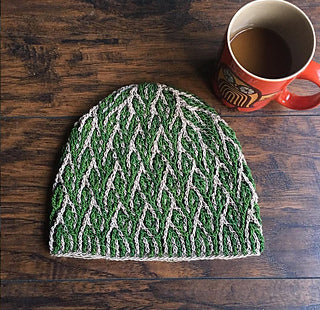 a crochet hat that looks like its covered in seaweed on a wooden table with a cup of tea or coffee in an orange mug on the top right