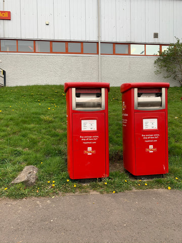 two royal mail, bright red parcel collection boxes with stainless steel parcel holes. they are on the right of the photo close together, about a foot. you can see some pavement in front of them, green grass to the side and behind and there is a big grey royal mail building with a row of tiny windows along the middle, it takes up the whole back of the photo