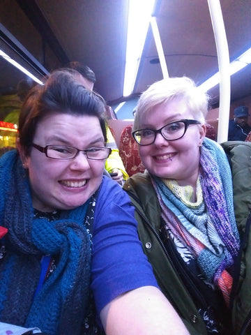 two women sat on a bus. the one on the left is me, i am grinning like an idiot, wearing glasses, a blue top and dark grey shawl my hair is dark brown. Hannah is on the right wearing a green kaki jacket a rainbow coloured shawl glasses and bleach blonde hair