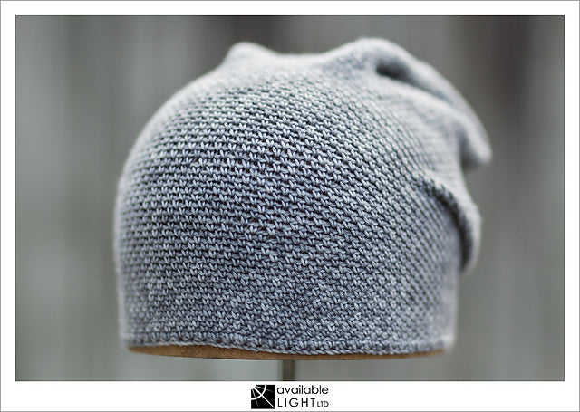 very simple image of a grey crochet hat on a wooden dome.