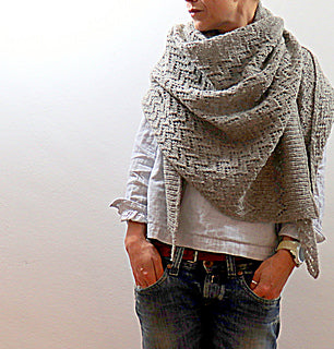women stood against a white background with hands in her jeans pockedts with a white linnen top wearing a beutfully natural light grey shawl