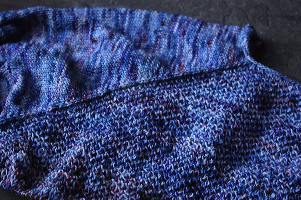 Maema-by-Megan-Dodecker top left hand side of a half knit cardigan laying on a dark floor, the cardigan is royalish blue with little orange speckles