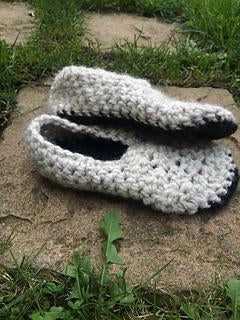 two light grey crochet slippers with dark black soles one resting ontop of the other. sat on an outside path surrounded by grass