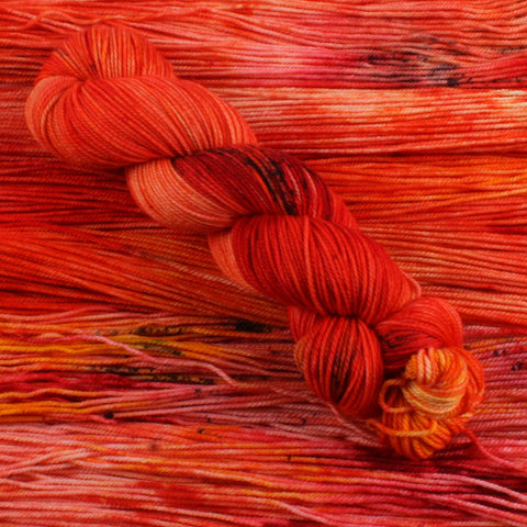 a skein of yarn is sitting diagonal to the image. it is orange and read wth some peach. really vibrant, also a small speckle of black. it is sitting ontop unowund yarn of the same colour