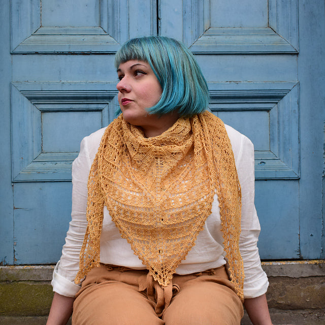 a women with blue hair sat infront of a blue door wearing a light orange shawl that is of beautful lace
