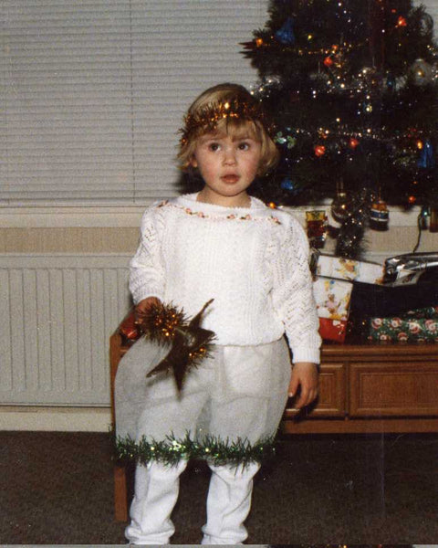 young lj maybe 3 or 4 dressed up as the christmas tree star. im wearing a white top. white tights and a tule net skirt trimmed with green tinsel. i have a gold tinsel head band and a gold star. cute a f
