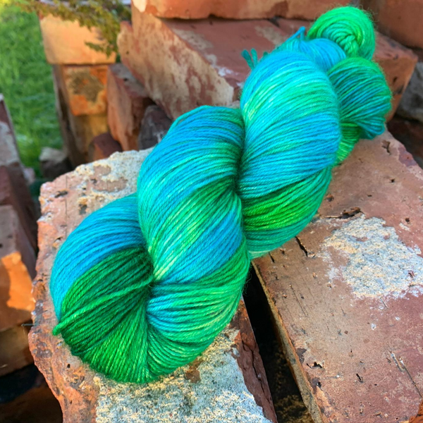 a skein of blue and green yarn sitting on a pile of bricks