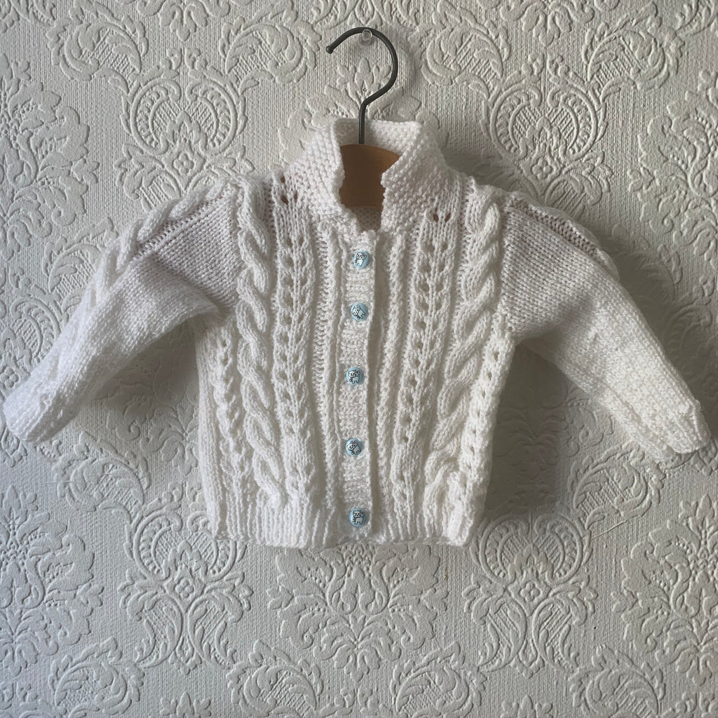 tiny white baby cardigan pinned up by an old wooden coat hanger against a white puff wallpaper. the cardigan is covered in cables and a wee collar. the buttons are baby blue with tiny vintage cat faces on them